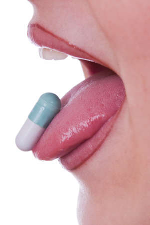 antibiotic pills: Woman open mouth with a pill on the tongue