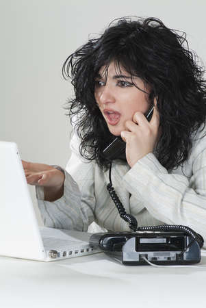 Businesswoman talking on the phone looking horrified her laptop photo