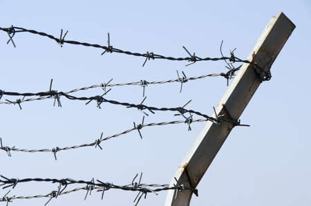 Protected fence with barbed wire on blue sky background photo