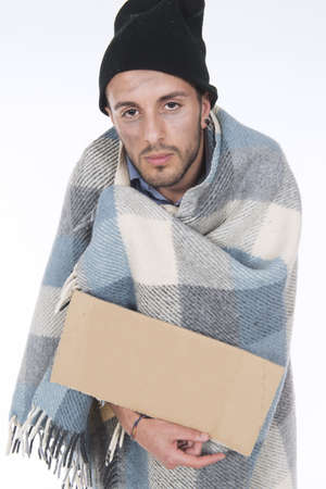 uncoordinated: Shooting in studio Homeless wrapped in his blanket begging with a sign