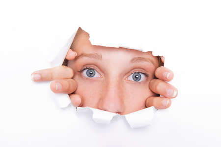 Young woman looks through a hole formed in the white paper