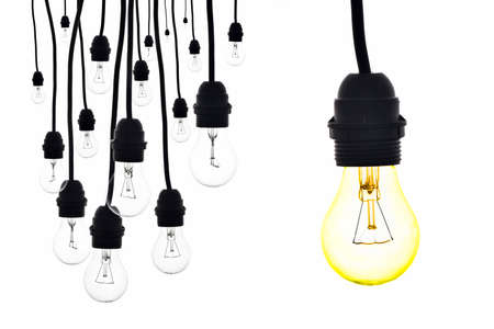 A yellow light bulb next to a number of light bulbs hanging on white Standard-Bild