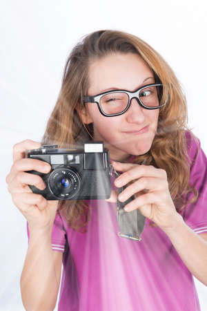 Young nerd photographer with camera in hand which make a flash photo