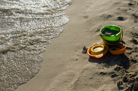 playthings: Beach toys left on the shore near the undertow