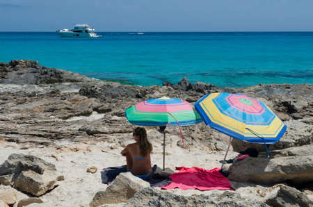 observes: Girl on the beach of sand and rocks sitting next to umbrellas observes speedboat off