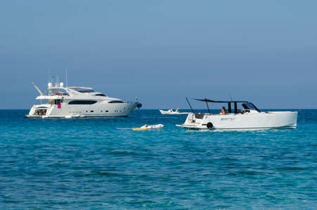 speedboats: Some Speedboats and yachts moored off on a blue sea