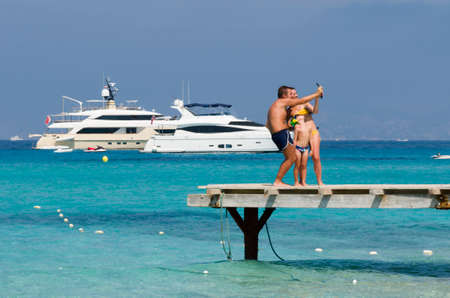 speedboats: Formentera, Spain, Plaja de ses Illetes - July 20, 2015: Family during the holidays makes selfie on a pier, in the background Speedboats moored in a sea blue and green