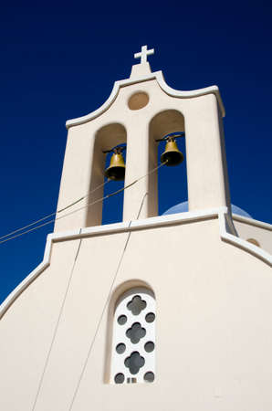 church bells: Ropes attached to the bells of a bell tower in front of the blue sky of a church in Santorini Greece Stock Photo