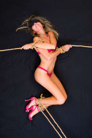 erotic fantasy: Woman in lingerie and high-heeled shoes blindfolded and bound hand and foot on the bed