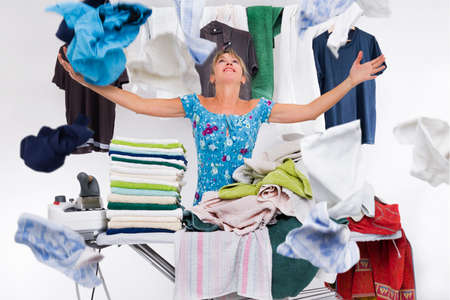 woman behind an ironing board packed with towels iron launches top clothes just ironed Standard-Bild