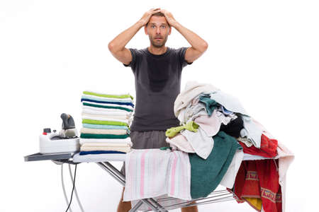 all sweaty and desperate man puts his hands through his hair because he has to stretch a stack of towels placed on a ironing board