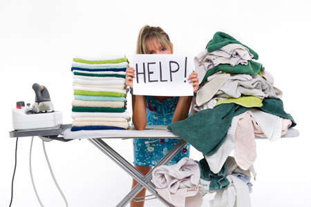 Woman behind a table covered with clothes to be ironed, displays a sign with help 스톡 콘텐츠