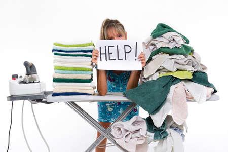 agotado: Mujer detrás de una mesa cubierta con ropa a planchar, muestra un cartel con ayuda