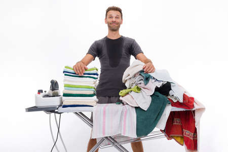 crazed: sweaty man, satisfied and proud, behind a ironing board where they are placed towels placed on a ironing board Stock Photo