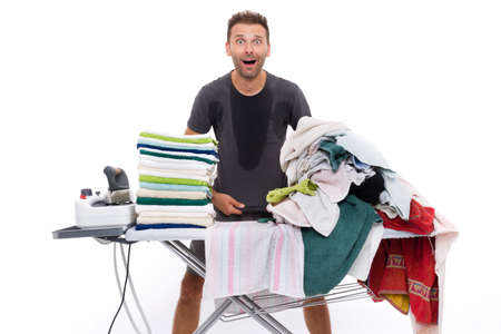 all sweaty and desperate man to iron a stack of towels placed on a ironing board