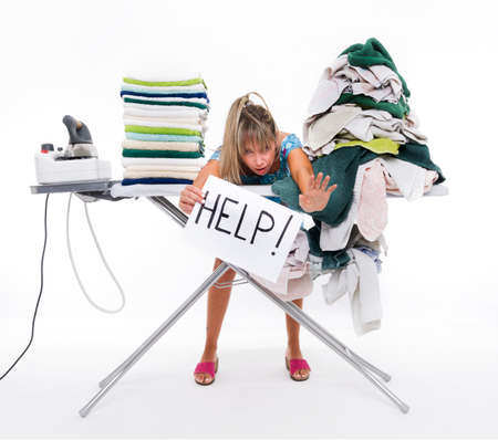 Woman behind a table covered with clothes to be ironed, displays a sign with help Stockfoto