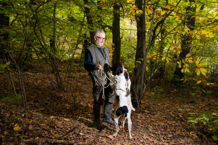 Elderly man caresses his dogs while looking for truffles in the woods