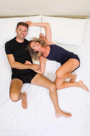 mujer en la cama: Pareja feliz y sonriente, de la mano en la vista superior cama
