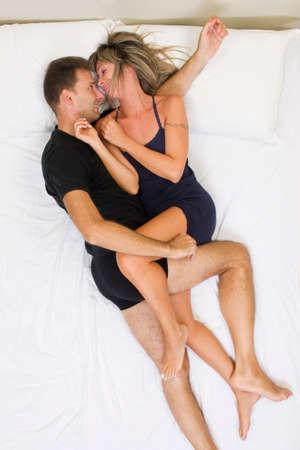 Esposas: feliz pareja sonriendo y abrazándose en la vista superior cama Foto de archivo