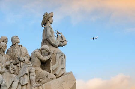 caravel: Discoverers Monument, Lisbon, Portugal, in the background a airplane flying in the blue sky at the statue