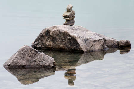 rocks water: Pieces of stacked rocks are reflected in the water