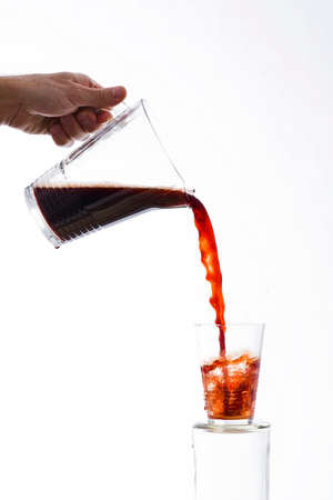 exaggerated: Drink poured from a jug into a glass on white background Stock Photo