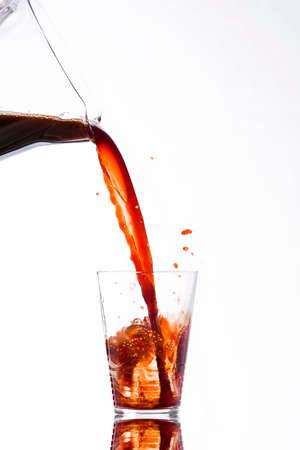wallop: Drink, vigorously poured from a carafe, overflowing splashing from a glass, on a white background