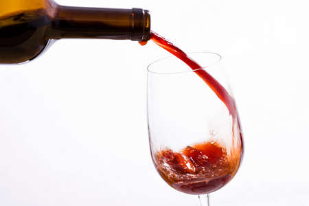wallop: Wine poured from a bottle in a wine glass, on a white background