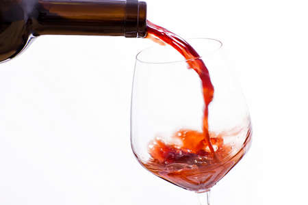 waterfall: Wine poured from a bottle in a wine glass, on a white background
