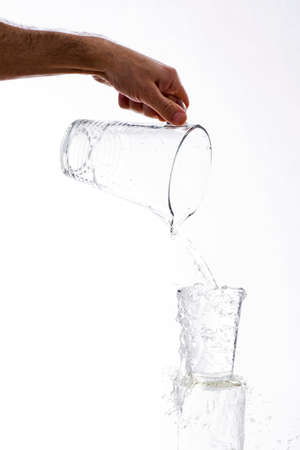 overflowing: Water, vigorously poured from a jug overflowing splashing from a glass, on a white background
