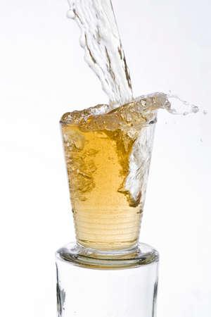 vigorously: Tea drinks poured vigorously overflowing splashing from a glass, on a white background