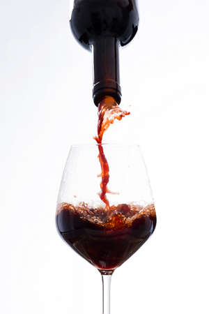 wallop: Vigorously wine poured from a bottle in a wine glass, on a white background