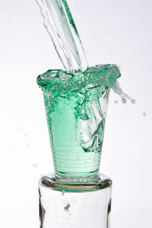 vigorously: Green drinks poured vigorously overflowing splashing from a glass, on a white background