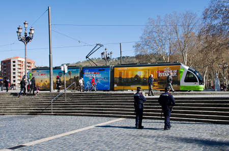 local 27: Bilbao, Spain - March 27, 2016: Local electric tramway with advertising to travel to Turkey, on the square two policemen