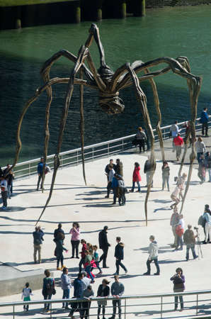 bourgeois: Bilbao, Spain - March 28, 2016: Maman sculpture, by Louise Bourgeois, Guggenheim Museum, Between the legs, numerous people