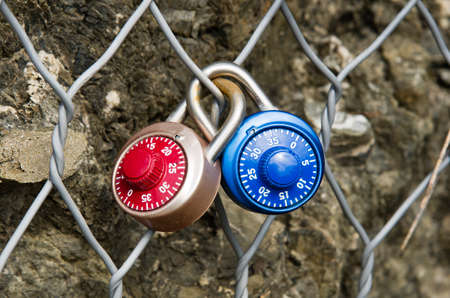 combination: Two colored locks numerical combination, closed on a metal grid one inside the other