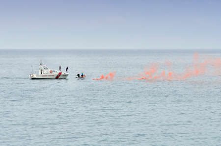 triggered: Liguria, Italy, June 5, 2016: Coast Guard ship, save to a small boat that triggered a red signal smoke