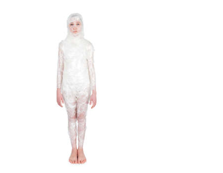 cellophane: Little girl standing wrapped in transparent film like a mummy on a white background