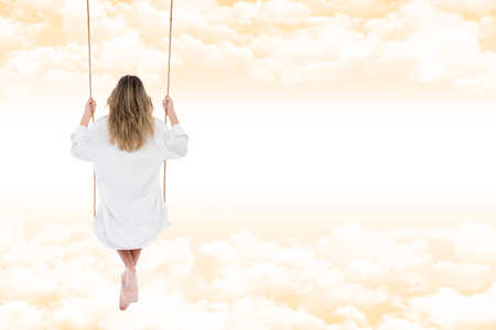 Blonde woman thoughtful and relaxed, back view, dressed in white shirt for men, on the swing, suspended through the clouds of a fantasy and warm amber sky
