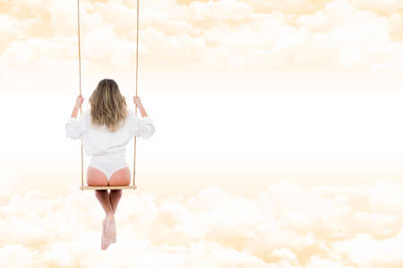 warm shirt: Blonde woman thoughtful, relaxed, back view, wearing shirt and white panties, on the swing, suspended through the clouds of a fantasy and warm amber sky