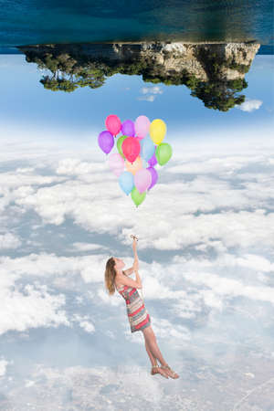 top of the world: Girl hanging by a bunch of balloons flying toward a world upside down, in the below there is the earth, at the top there is an island in the sea Stock Photo