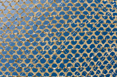 obscure: Detail of a beige camouflage grid paper, on the bottom blue sky