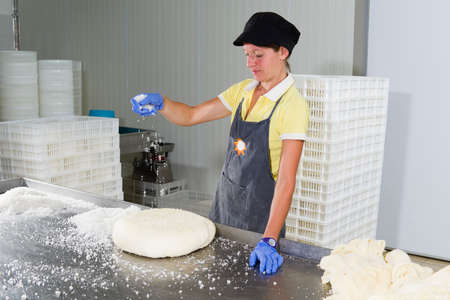 food industry: Woman is putting same salt on the pieces of cheese for the maturing Stock Photo