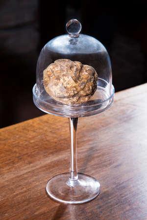 truffe blanche: truffe blanche à l'intérieur de la cloche de verre d'emballage sur la table en bois