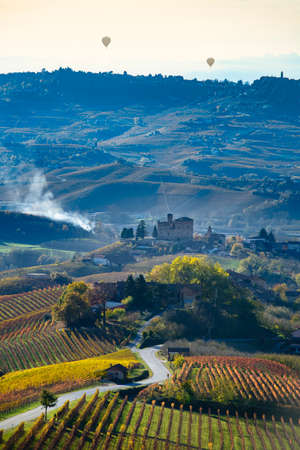 Grinzane Cavour, Italy - November 12, 2016: Road between the hills of Langa Piemonte Italy, at the bottom the castle of Grinzane cavour, in the sky two balloons Editorial