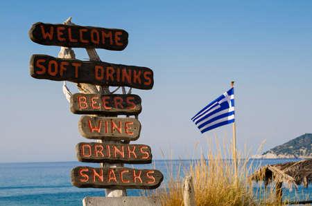 바닷가에있는 나무 표지판은 Skiathos, 그리스의 음식과 음료를 제공하는 술집의 존재를 나타냅니다. 하단에는 그리스 국기 스톡 콘텐츠