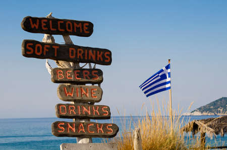 Wooden signposts on the beach indicate the presence of a bar offering food and drink in Skiathos, Greece, on the bottom the Greek flag