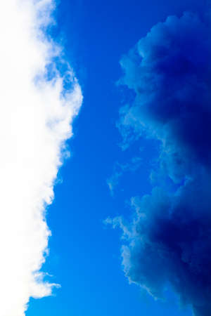 Contrast between white and dark blue clouds, still rainy after a violent thunderstorm in a clear blue sky