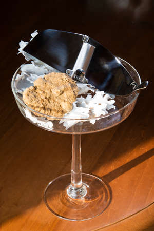 Wonderful white truffle on a glass cup with pedestal, with truffles cut in silver steel, on wooden table, from Langhe Alba in Piedmont Italy. Stock Photo