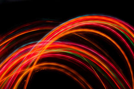 Trails of multicolored radial lights blurred on black